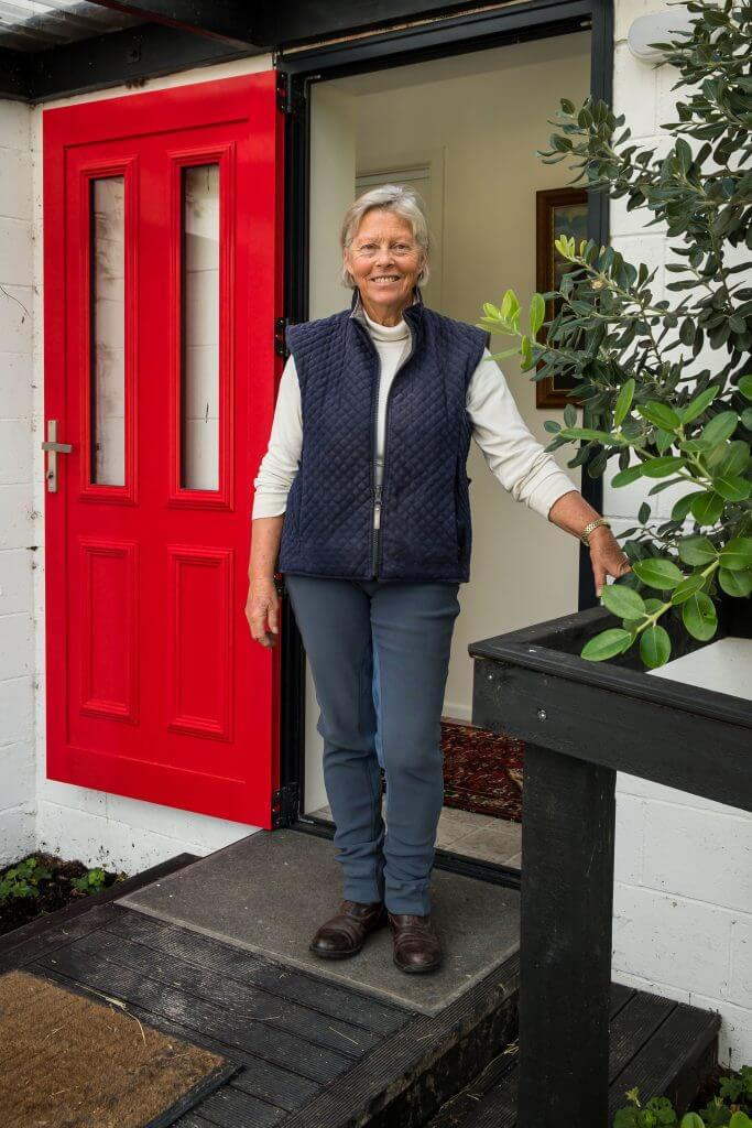 Mandy Robinson in front of the red door of Te Horo Farmstay